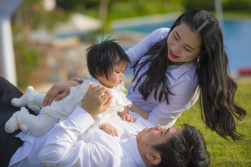 Unga gladlynta och söta fru- och makepar med modern och fadern som spelar med den lilla dottern i asiatisk koreansk familj royaltyfria foton