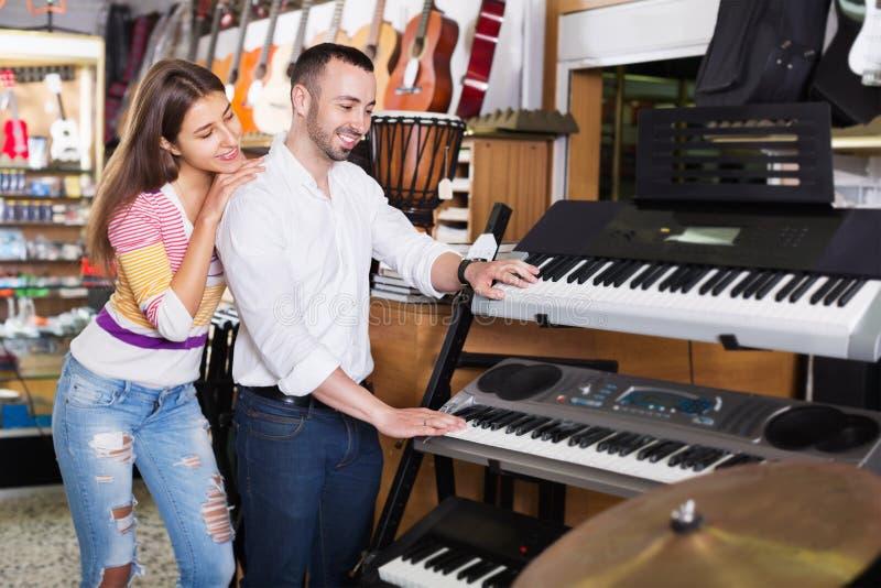 Unga gladlynta par som väljer syntet shoppar in royaltyfria foton