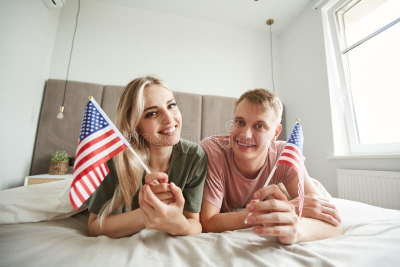 Unga gladlynta patrioter med amerikanska flaggan som ligger på säng royaltyfri bild