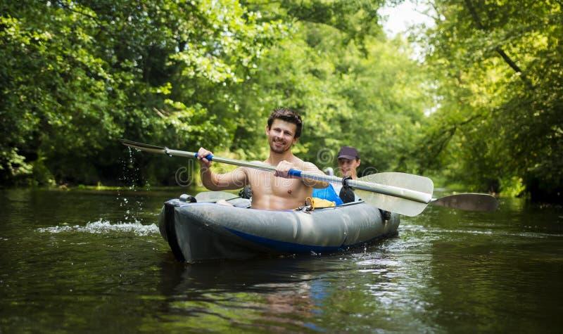 Unga grabbar i fartyg med åror på floden mot bakgrund av gröna träd över vatten Kayakers i kajak royaltyfria bilder