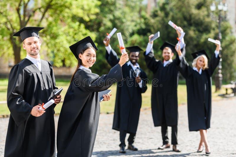 unga graderade studenter som tillsammans står, i trädgård och att se för universitet royaltyfri bild