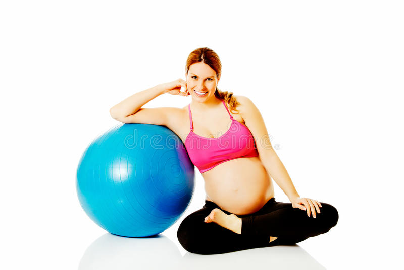 Unga gravid kvinnaexcercises med den gymnastiska bollen royaltyfri fotografi