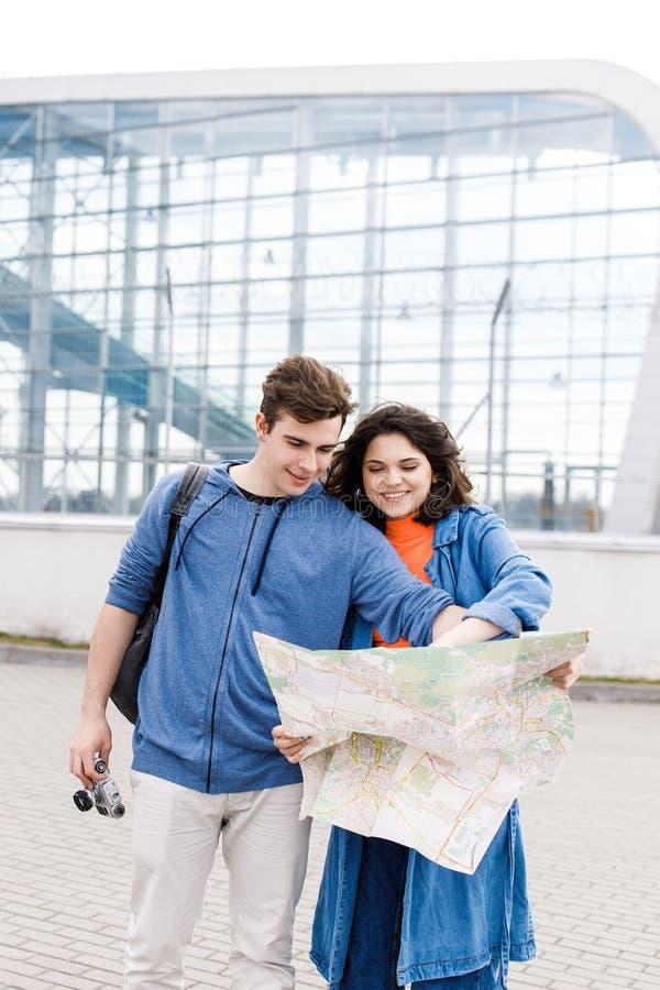 Unga gulliga par - en pojke och en flicka som går runt om staden med en översikt och kamera i deras händer Ungdomarreser royaltyfri fotografi