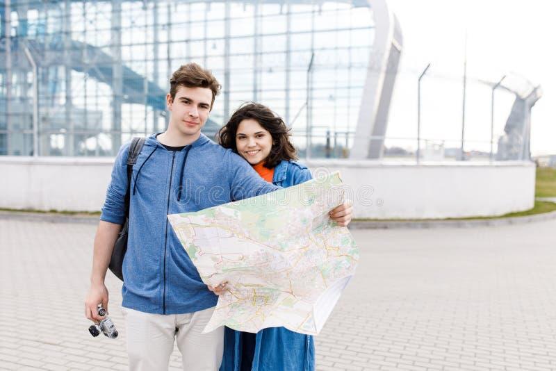 Unga gulliga par - en pojke och en flicka som g?r runt om staden med en ?versikt och kamera i deras h?nder Ungdomarreser arkivbilder
