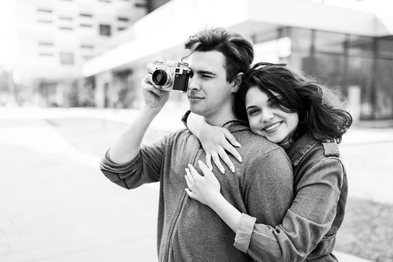 Unga gulliga par - pojke och flicka som går runt om staden och en fotograferar Ett par har rolig utgiftertid tillsammans Datum tv royaltyfri foto