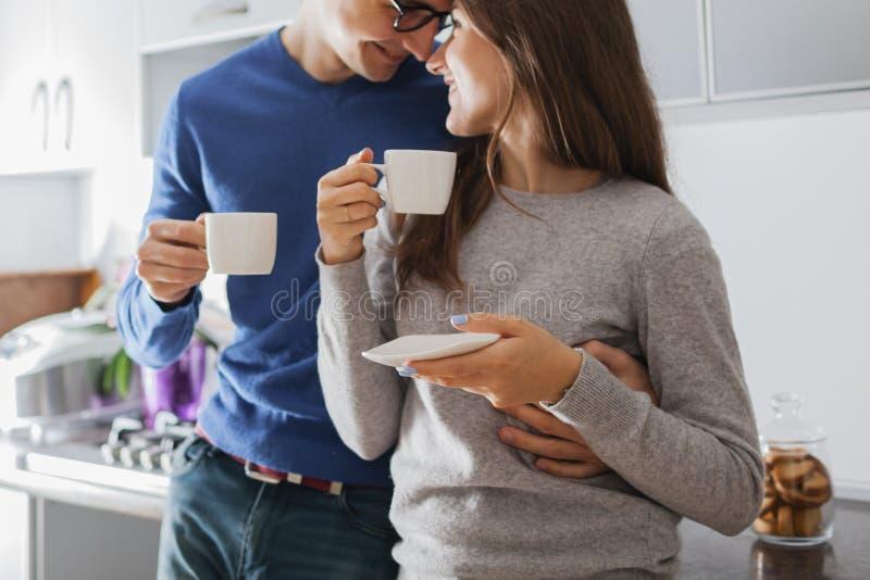 Unga gulliga par som kramar och dricker te i k?ket royaltyfri fotografi