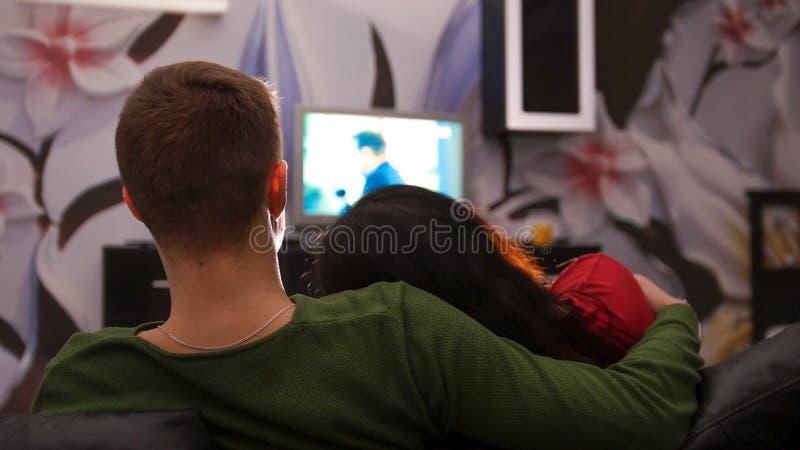 Unga gulliga par som tillsammans sitter på en hållande ögonen på TV för soffa Kvinnan lägger på hennes pojkvänskuldra arkivfoto