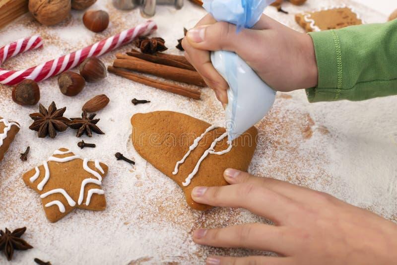 Unga händer dekorerar kakor för gingerbröd med vit ikon från plastpåse royaltyfri bild