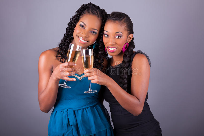 Unga härliga afrikanska kvinnas innehav per exponeringsglas av champagne arkivfoto