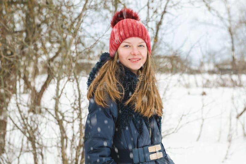 Unga härliga blonda flickaställningar och leenden i parkerar under mjuk fluffig snö på en kall vinterdag arkivbilder