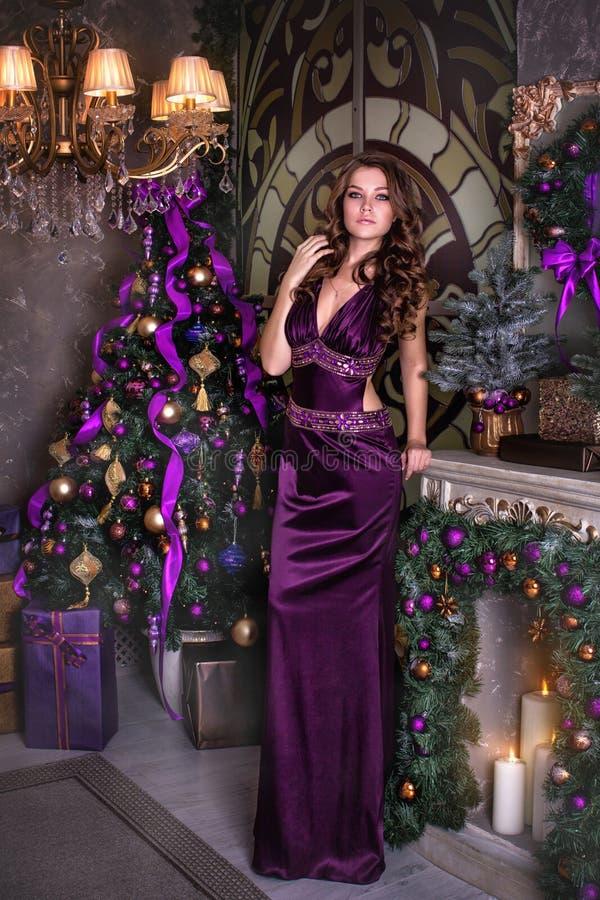 Unga härliga brunettkostnader i en violett lång klänning nära ett julgran-träd Närliggande de bränningstearinljusen och gåvorna royaltyfri foto