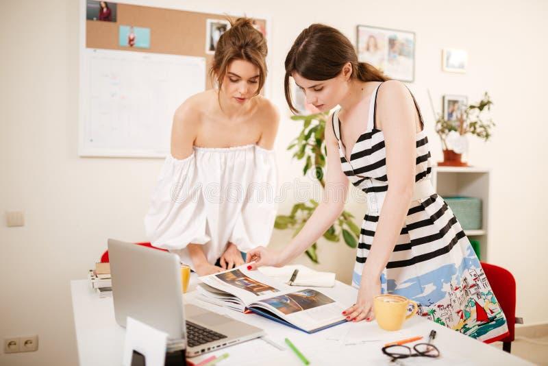 Unga härliga flickor som ser hänsynsfullt i bok med bärbara datorn på tabellen som tillsammans i regeringsställning arbetar arkivfoto
