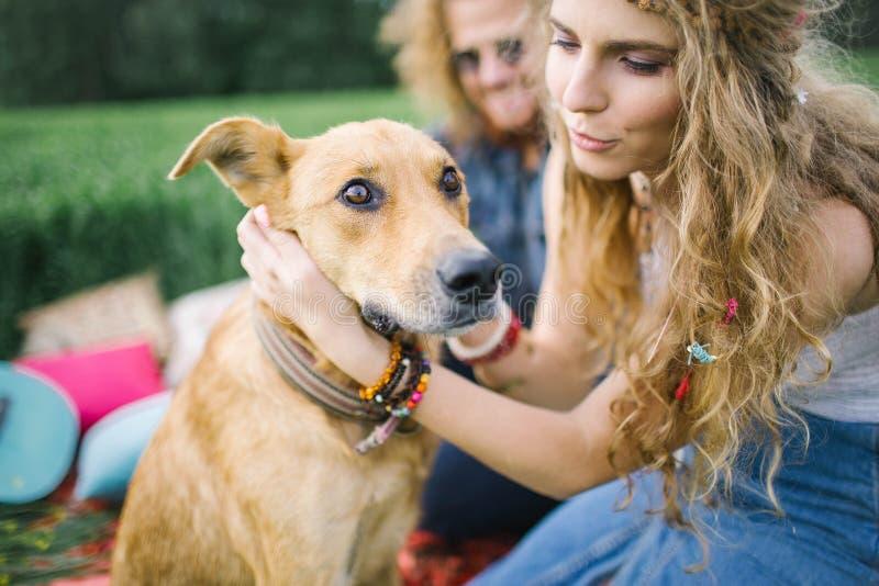 Unga härliga hippiepar med hunden i natur royaltyfria foton