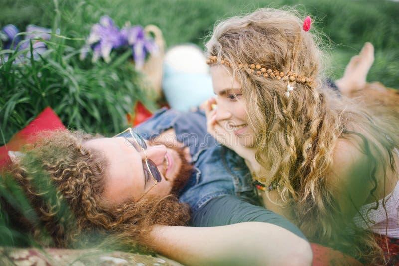 Unga härliga hippiepar som ligger på gräs som har gyckel arkivbilder