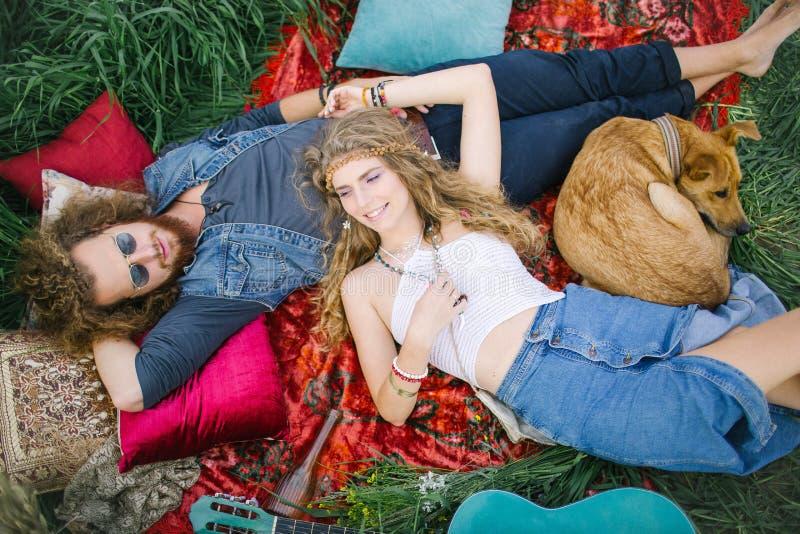 Unga härliga hippiepar som ligger på gräs som har gyckel royaltyfri bild