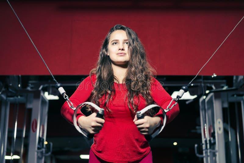 Unga härliga idrotts- flickadrev på simulatorn i idrottshallen sportig kvinna i röd damasker som gör övning arkivfoto