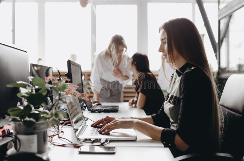 Unga härliga kvinnor som kläs enligt kontorsdreskod, arbetar på skrivborden med en dator och bärbara datorer i a arkivfoton