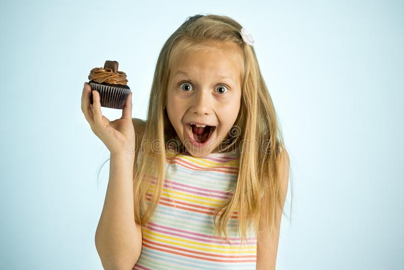 Unga härliga lyckliga och upphetsade blonda gammal hållande chokladkaka för flicka 8 eller 9 år på hennes hand som ser spastisk o fotografering för bildbyråer