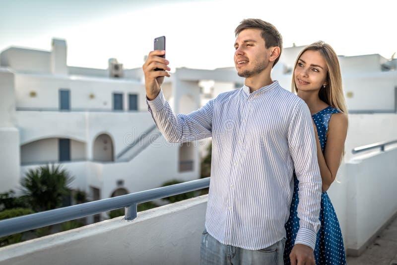 Unga härliga lyckliga parbloggers som ler göra selfie, direktanslutet att sända som poserar, meddelar Grabben rymmer mobilt royaltyfri bild