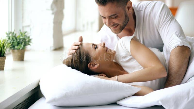 Unga härliga och älska par vaknar upp på morgonen Den attraktiva mankyssen och kramar hans fru i säng arkivbilder