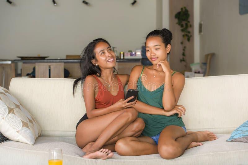 Unga härliga och lyckliga asiatiska flickvänner kopplar ihop eller systrar som tycker om socialt massmedia för internet som har g royaltyfri fotografi