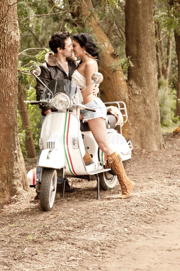 Unga härliga par med sparkcykeln längs grusvägen fotografering för bildbyråer