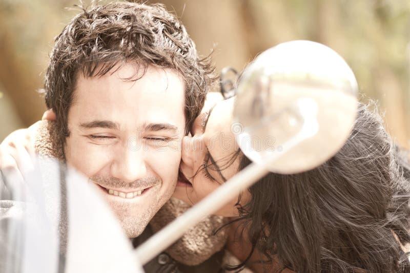Unga härliga par som flörtar och har gyckel med sparkcykeln royaltyfri foto