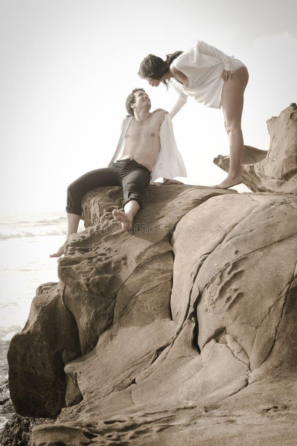 Unga härliga par som flörtar på stranden fotografering för bildbyråer