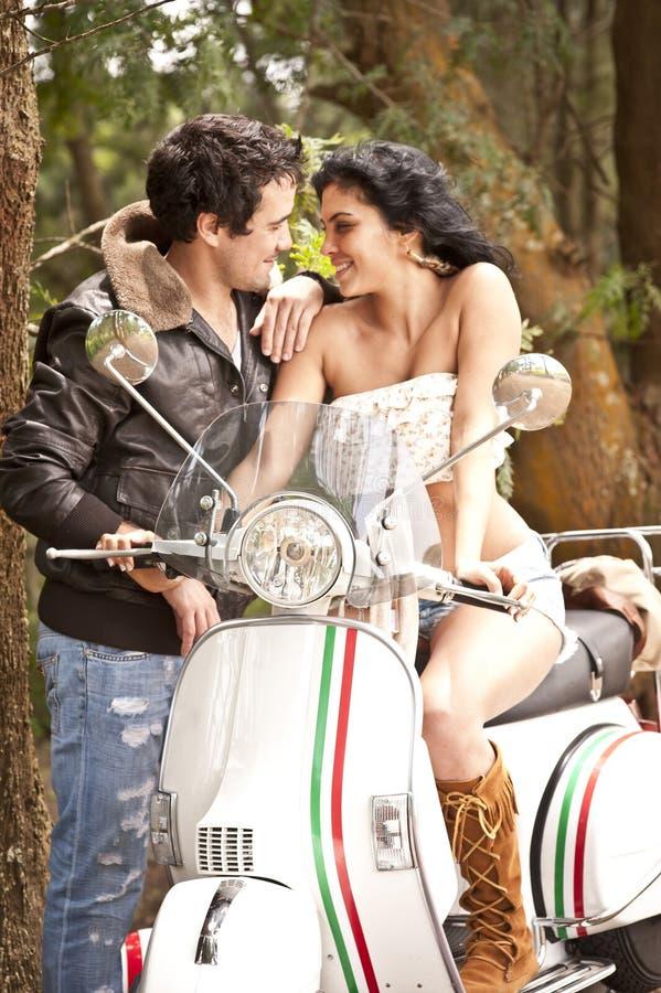 Unga härliga par som har rolig det fria med sparkcykeln royaltyfria bilder