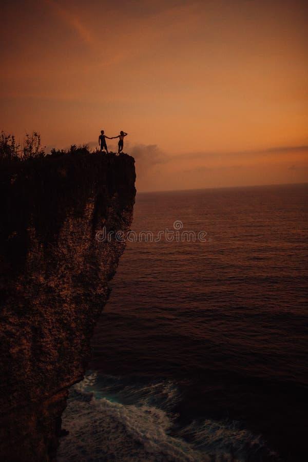 Unga härliga par som kysser på solnedgången nära havet, kontur arkivbilder