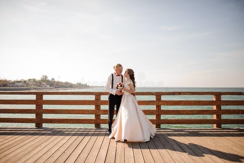 Unga härliga par som omfamnar på träbron i bakgrund av havet royaltyfri foto
