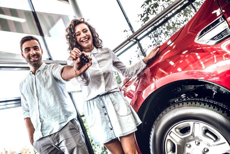 Unga härliga par som rymmer biltangent och ser kameran med leende, medan stå inomhus med bilen på bakgrunden arkivbilder