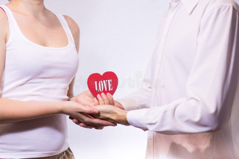 Unga härliga par som rymmer röd hjärta royaltyfri fotografi
