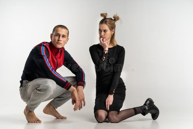 Unga härliga par som sitter på golvet, studiostående royaltyfri foto