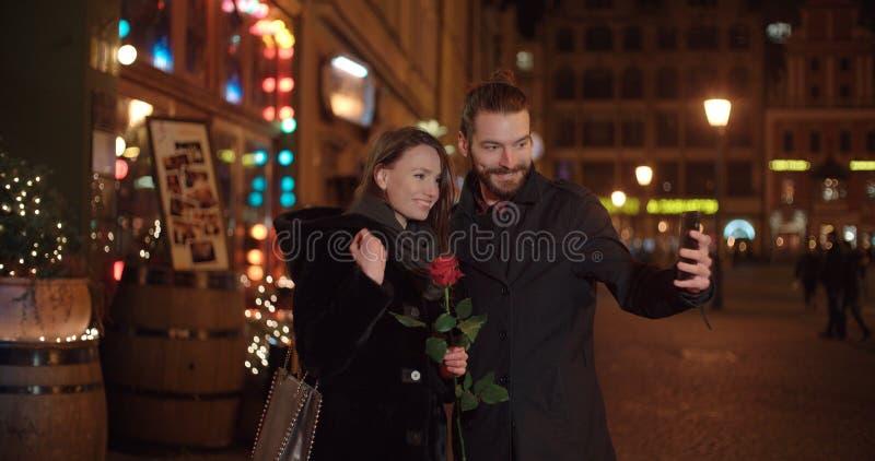 Unga härliga par som tar selfie i en stad på natten royaltyfria foton