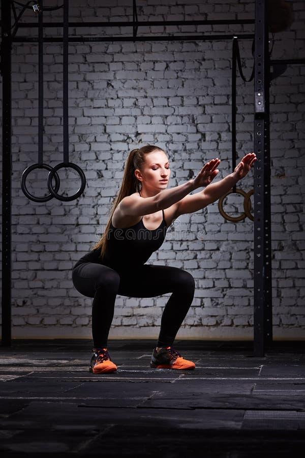 Unga härliga sportiga kvinnadanandesquats mot tegelstenväggen i kors passade idrottshall royaltyfri bild
