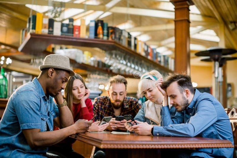 Unga högskolestudenter eller coworkers som tillsammans använder smartphones på coffee shop, olik grupp Tillf?llig aff?r, frilans fotografering för bildbyråer