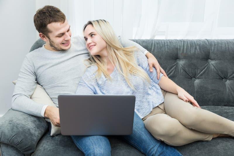 Unga h?rliga par som vilar p? soffan och den h?llande ?gonen p? online-videoen fr?n en b?rbar dator i vardagsrummet arkivfoto