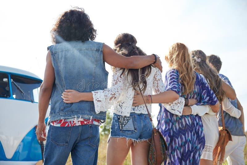 Unga hippievänner som kramar över minivanbilen royaltyfria foton