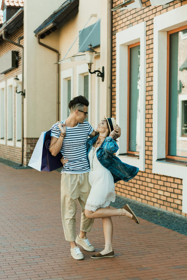 Unga hipsterpar med shoppingpåsar som ser de och kramar på gatan arkivbilder
