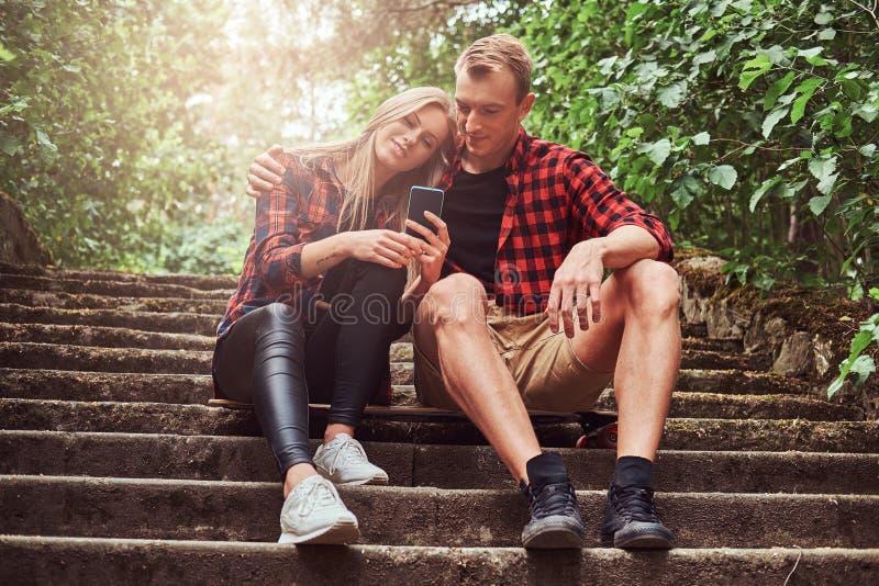 Unga hipsterpar, stilig grabb och flicka för skönhet som blond vilar sammanträde på momenten i en parkera, en kel och se arkivfoto