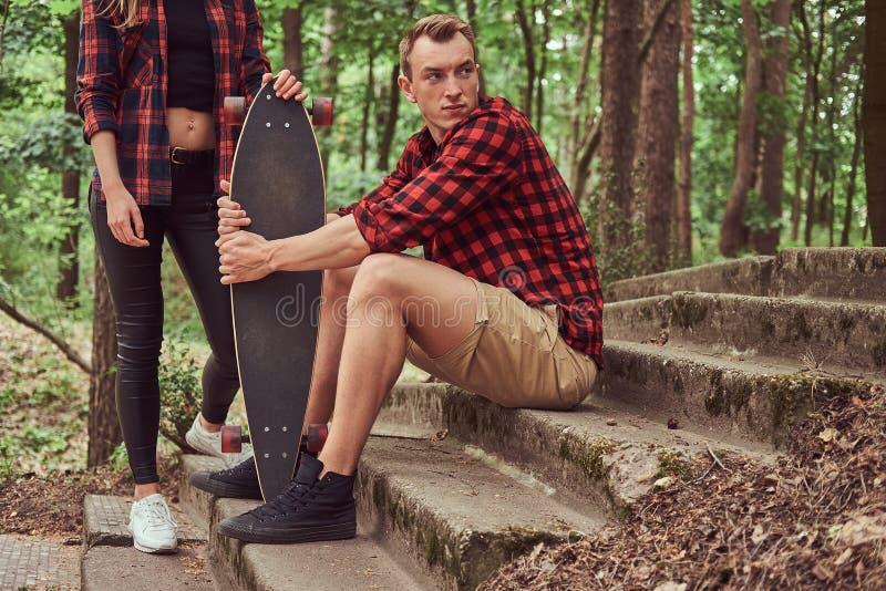 Unga hipsterpar, stilig man med en skateboard och blondinflicka som sitter på moment i en parkera fotografering för bildbyråer