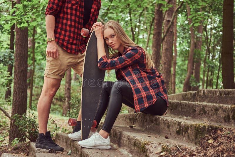 Unga hipsterpar, stilig man och blondinflicka med en skateboard som sitter på moment i en parkera royaltyfria bilder