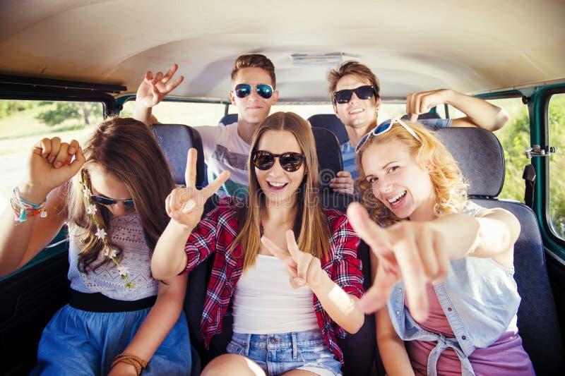 Unga hipstervänner a på vägtur royaltyfria foton