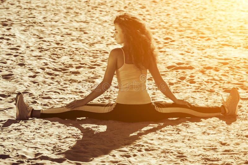 Unga idrottsman nen - gymnast med lockigt hår och gymnastikskor som gör splittringarna på stranden i sommarmorgonövning arkivfoto