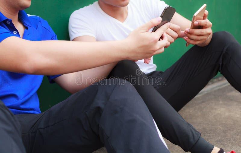 Unga idrottsman nenmän som arbetar på smartphonen, medan vila i sportklubba Mobilt kontor, frilans, livsstil, internetmarknadsför arkivbild