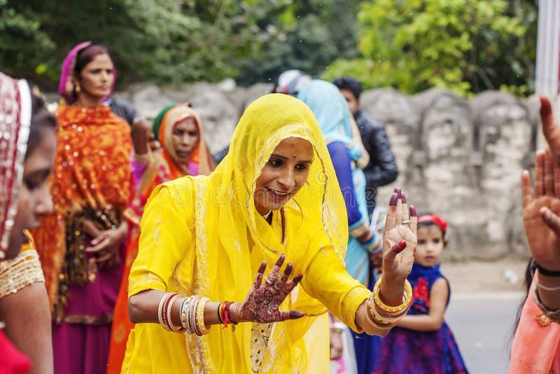 Unga indiska flickor i den traditionella sari som dansar på bröllopfolkmassan på gatan royaltyfri foto