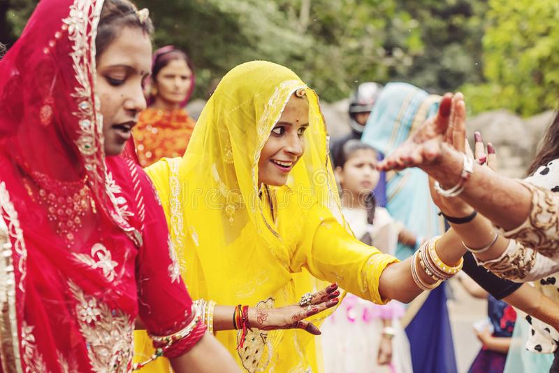 Unga indiska flickor i den traditionella sari som dansar på bröllopfolkmassan på gatan royaltyfria bilder