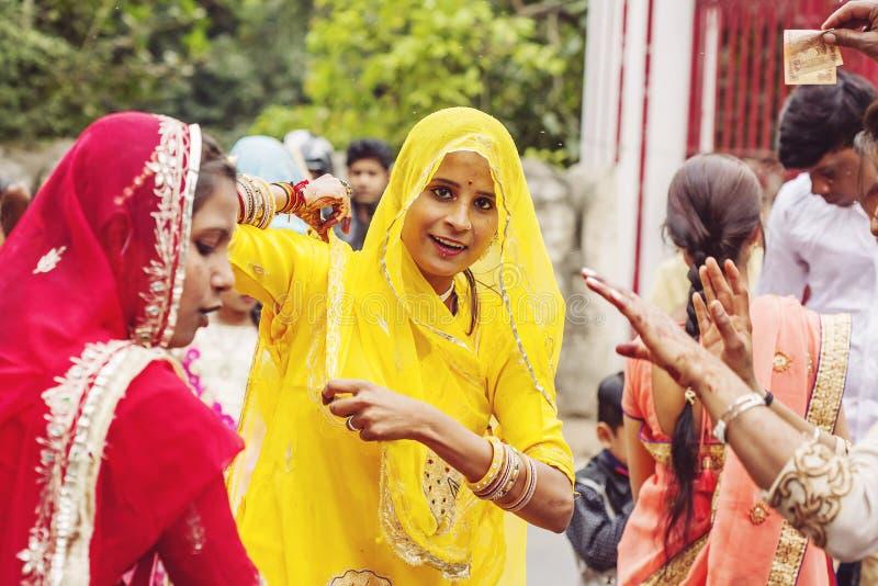 Unga indiska flickor i den traditionella sari som dansar på bröllopfolkmassan på gatan arkivfoton