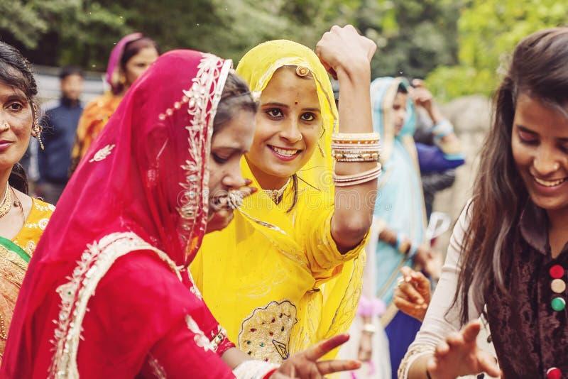 Unga indiska flickor i den traditionella sari som dansar på bröllopfolkmassan på gatan royaltyfri bild